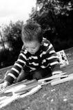 Weißer Junge, der Alphabet im Park erlernt Lizenzfreie Stockfotografie