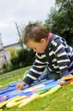 Weißer Junge, der Alphabet im Park studiert Stockfoto