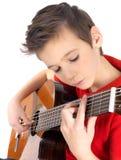 Weißer Junge, der auf Akustikgitarre spielt Stockfotografie