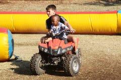 Weißer Junge, der schwarzem Jungenreiten auf Viererkabelfahrrad hilft Lizenzfreies Stockbild