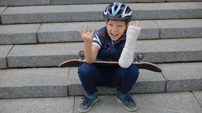 Weißer Junge mit defektem Arm makng das Felsenzeichen stock video footage