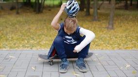 Weißer Junge mit dem gebrochenen Arm setzte sich von seinem Sturzhelm stock video footage