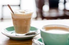 Weißer Kaffee in transparentretro Glas auf grünem Topf und hölzernem t Stockbilder
