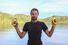 Weißer kaukasischer männlicher Reisender in der Sportkleidung, die zwei Hälften der Avocado mit Samen vor dem hintergrund des See stockfotos