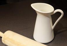 Weißer keramischer Milchkrug mit Nudelholz Lizenzfreies Stockbild