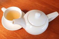 Weißer keramischer Teetopf und Teeschale auf hölzernem Hintergrund Lizenzfreie Stockbilder