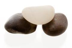 Weißer Kiesel oben auf zwei dunkle Kiesel Lizenzfreies Stockbild