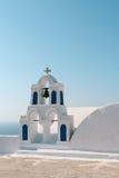 Weißer Kirchenglocketurm mit blauem Himmel in Oia, Santorini, Griechenland stockbild