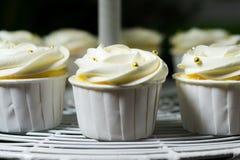 Weißer kleiner Kuchen auf cakestand gegen dunklen Hintergrund, Nahaufnahme Lizenzfreies Stockfoto