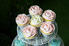 Weißer kleiner Kuchen, rosa kleiner Kuchen und blauer kleiner Kuchen auf cakestand gegen dunklen Hintergrund Stockbild
