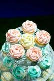 Weißer kleiner Kuchen, rosa kleiner Kuchen und blauer kleiner Kuchen auf cakestand gegen dunklen Hintergrund Stock Abbildung