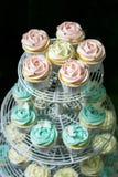 Weißer kleiner Kuchen und blauer kleiner Kuchen auf cakestand gegen dunklen Hintergrund, Nahaufnahme Lizenzfreie Stockfotografie
