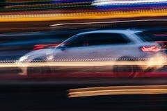 Weißer Kleinwagen in einer unscharfen Stadt-Szene Lizenzfreie Stockfotografie