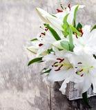 Weißer Korb mit weißer Lilie blüht Blumenstrauß auf rustikalem hölzernem t Stockfotos