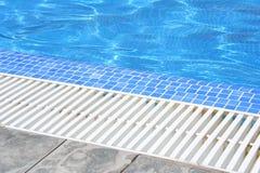 Weißer kratzender Grill des Swimmingpools mit klarem blauem Wasser und grauen Fliesen Stockbilder