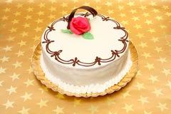 Weißer Kuchen auf goldenem Sternhintergrund Stockbild
