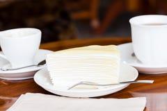 Weißer Kuchen auf weißem Teller mit Gabel, Serviette auf Tabelle Stockfotografie
