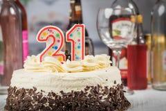 Weißer Kuchen mit chooclate Dekorationen und 21 Kerzen Alcoholi Stockfotos