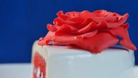 Weißer Kuchen mit Schokoladenverzierungen und rotem Marzipan stieg auf dunkelblauen Hintergrund Kuchen verziert mit essbaren rote Stockbild