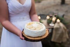 Weißer Kuchen mit Zitronen in der Hand einer Braut Kuchen auf einem hölzernen Behälter Stockfotos