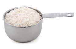 Weißer langkörniger Reis dargestellt in einem amerikanischen Metallcupmaß Lizenzfreie Stockbilder