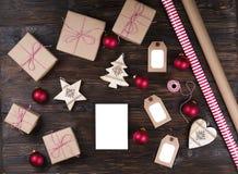 Weißer Leerbeleg mit Weihnachtsgeschenken auf Draufsicht des hölzernen Hintergrundes, flache Lage Weihnachtsgeschenkliste, Sankt- stockfotografie