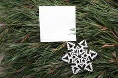 Weißer leerer Rahmen und dekorative Schneeflocke auf grüner Kiefer verzweigt sich Hintergrund Stockfotografie