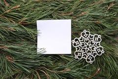 Weißer leerer Rahmen und dekorative Schneeflocke auf grüner Kiefer verzweigt sich Hintergrund Stockfoto