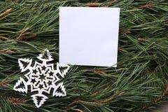 Weißer leerer Rahmen und dekorative Schneeflocke auf grüner Kiefer verzweigt sich Hintergrund Stockbilder