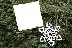 Weißer leerer Rahmen und dekorative Schneeflocke auf grüner Kiefer verzweigt sich Hintergrund Lizenzfreies Stockfoto