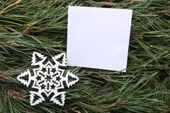 Weißer leerer Rahmen und dekorative Schneeflocke auf grüner Kiefer verzweigt sich Hintergrund Lizenzfreie Stockfotografie