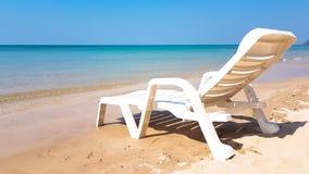 Weißer Lehnsessel auf dem nassen Strand in der sonnigen Zeit Stockfotos
