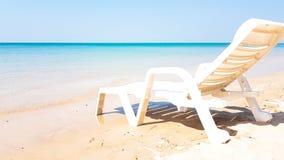 Weißer Lehnsessel auf dem nassen Strand in der sonnigen Zeit Lizenzfreies Stockfoto