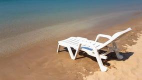 Weißer Lehnsessel auf dem nassen Strand in der sonnigen Zeit Stockbilder