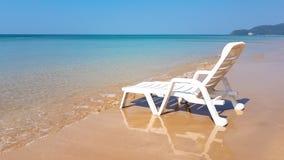 Weißer Lehnsessel auf dem nassen Strand in der sonnigen Zeit Stockbild