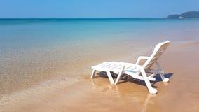 Weißer Lehnsessel auf dem nassen Strand in der sonnigen Zeit Lizenzfreie Stockfotografie