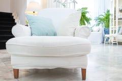 Weißer Lehnsessel mit Kissen im Wohnzimmer, Weinleseart Stockbilder