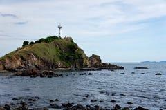 Weißer Leuchtturm auf einer Insel im Meer Stockfotografie
