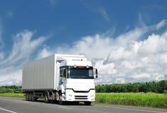 Weißer LKW auf Landdatenbahn unter blauem Himmel Lizenzfreie Stockfotografie