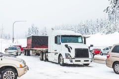 Weißer LKW auf Schneestraße mit Stau am schneebedeckten Tag Stockfotografie