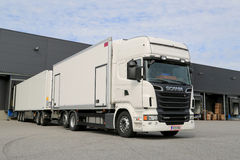 Weißer LKW Scanias R560, der am Lager-Gebäude entlädt Lizenzfreies Stockfoto