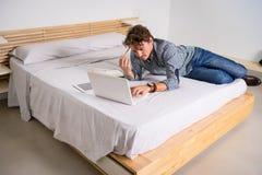 Weißer Mann, der im Bett mit seinem Computer liegt stockfotos