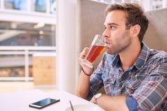 Weißer Mann, der weg von der Kamera beim Nippen an seinem Tee schaut Lizenzfreies Stockbild