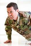 Weißer Mann im einheitlichen Belasten der Armee, einen Stoß oben tuend Lizenzfreies Stockfoto
