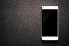 Weißer mobiler Smartphone auf schwarzem Luxushintergrund Stockfotografie