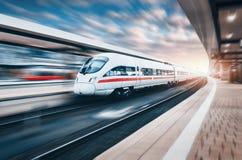 Weißer moderner Hochgeschwindigkeitszug in der Bewegung auf Bahnhof in SU Stockfotografie