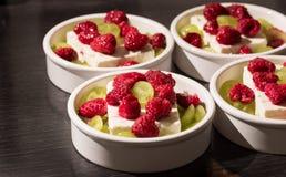Weißer Nachtisch rollt mit zwitschern ` s Käse, grüne Trauben und rote rasperries, bevor er im Ofen grillt Stockbild