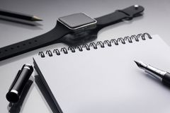 Weißer Notizblock auf ihm Schwarzstift nahe eine intelligente Uhr und Bleistift clos Lizenzfreie Stockfotos
