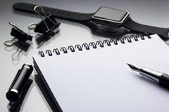 Weißer Notizblock auf ihm Schwarzstift nahe einer intelligenten Uhrnahaufnahme auf einem gl Stockfotos