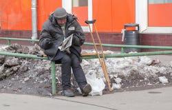 Weißer Obdachloser in Russland, in Moskau am 28. März, eine Zeitung lesend lizenzfreie stockfotos